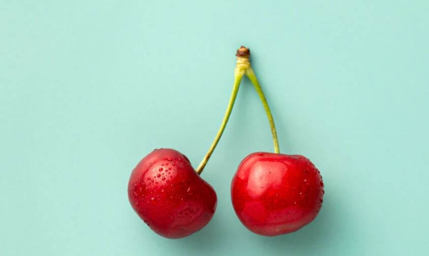 Two cherries on a light teal background